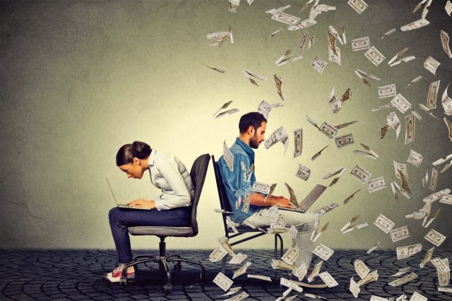 Men and woman on laptops with money in the air
