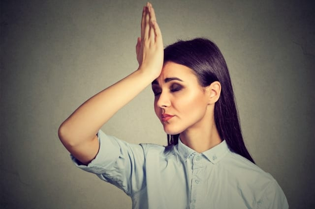 Woman with her hand to her forehead